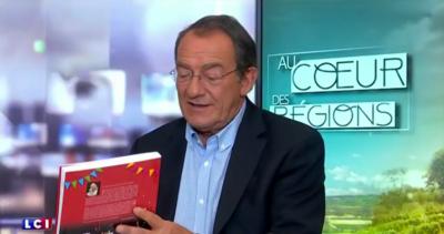 """Le livre """"LaGrande Aventure des Carnavaliers de Cholet"""" dans les mains de Jean-Pierre Pernaut sur LCI."""
